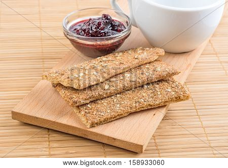 Crispbread fragment of white cup and jam in a vase.