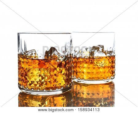 Glasses of whisky with ice isolated on white