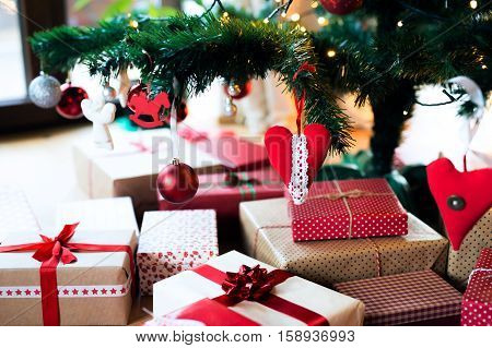 Close up of various Christmas presents in colorful wrapping papers lying on the floor under the illuminated Christmas tree.