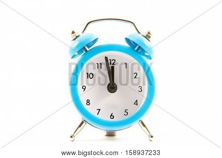 blue table clock on a white background three minutes to twelve