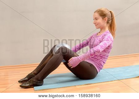 Fit Woman Is Doing Sit Ups With Medicine Ball Between Her Legs