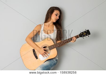 pretty girl with guitar in hands looking away in studio on grey background