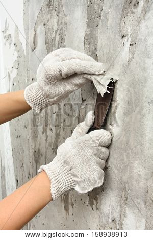 hands removing old wallpapers with spatula during repair