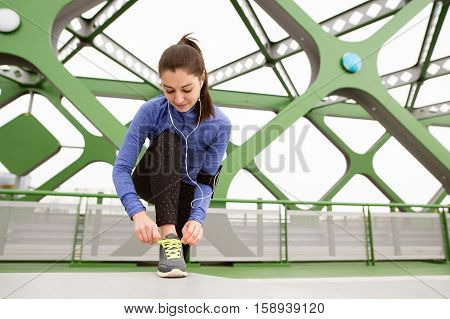 Beutiful runner in the city with earphones, listening music, tying shoelaces on green steel bridge. Close up.
