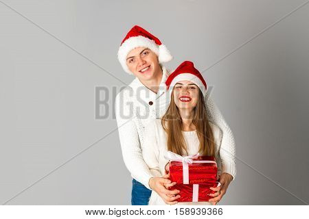 elegance couple celebrate christmas with gifts in studio on gray background