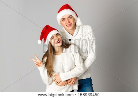 couple in love celebrates christmas and having fun in santa hats in studio on gray background
