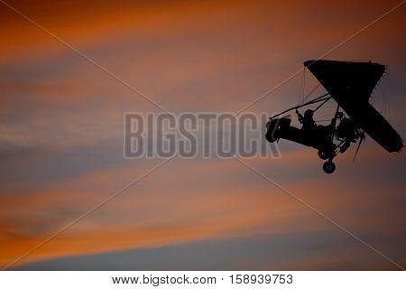 Hang glider flying in sky opposite sun at sunset