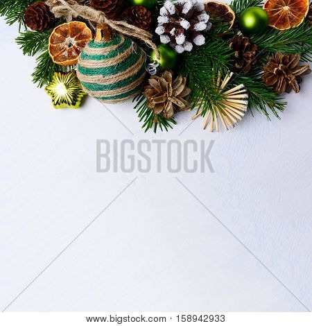 Christmas background with rustic ornaments and snowy decorated pinecone. Christmas background with fir branches. Copy space. Square.