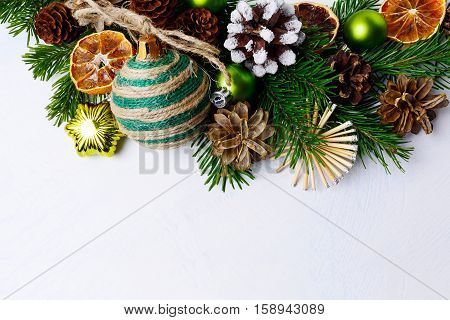 Christmas background with rustic ornaments and snowy decorated pinecone. Christmas background with fir branches. Copy space.