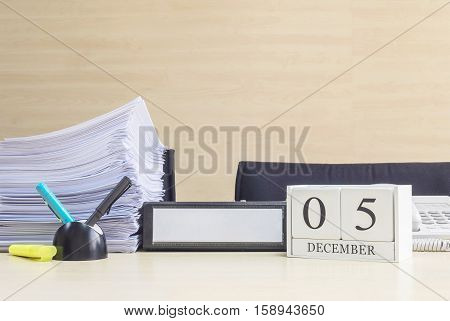 Closeup white wooden calendar with black 5 december word on blurred brown wood desk and wood wall textured background in office room view with copy space selective focus at the calendar