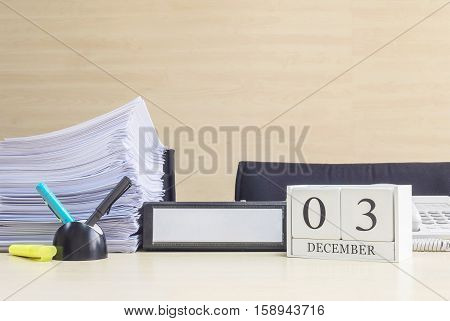 Closeup white wooden calendar with black 3 december word on blurred brown wood desk and wood wall textured background in office room view with copy space selective focus at the calendar