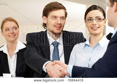 Photo of successful business partners handshaking after striking deal with pretty employees near by