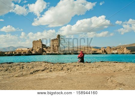 Woman in muslim hijab sitting near ruined city around the mountain lake, under white clouds