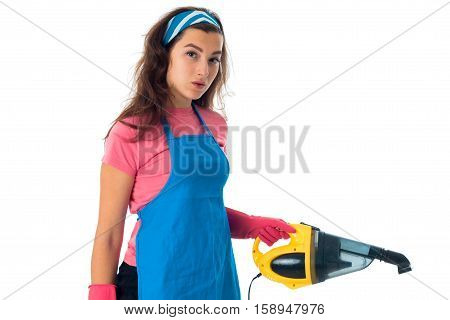 serious young maid woman in an apron with cleansers isolated on white background