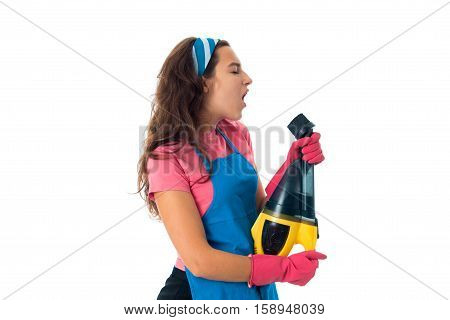 cheerful maid woman in an apron with cleansers isolated on white background