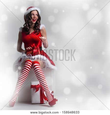 Pin-up Christmas woman in Santa Claus costume unpack gift