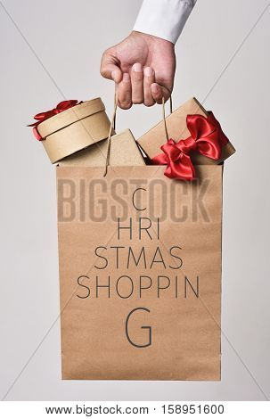 closeup of the hand of a young caucasian man holding a paper shopping bag full of gifts and the text christmas shopping written in it forming a christmas tree