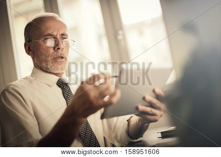 Businessman trying to solve problems on this tablet