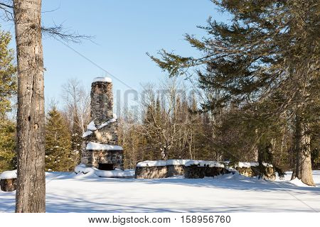Abandoned stone chimney in the woods in the winter. Remnants of a rural cabin.