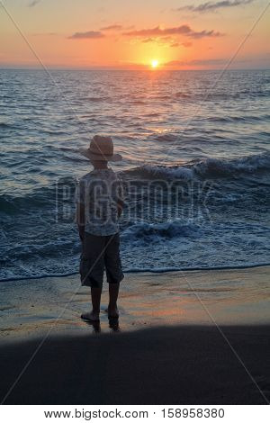 Small boy stands on the beach at the sundown, hands in the trouser pockets and looks to the horizon