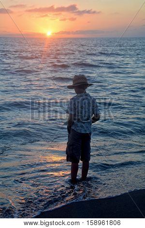 Small boy stands in the water on the beach at the sundown and looks in the water