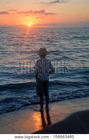 Small boy stands in the water on the beach at the sundown and looks as the sun