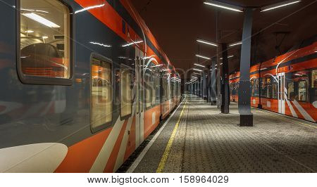 Railroad travel and transportation industry business concept: summer night view of two high speed modern passenger trains departing from railway station platform no motion, standing still.