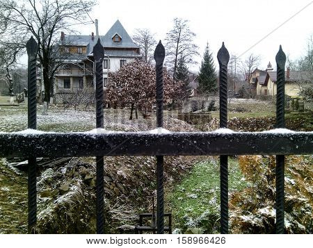 First snow. a Little of snow lies on the grass trees and fence around the two-story private house