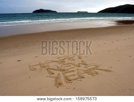 Happy new year written on sand at sunset. Happy New Year lettering on the beach.