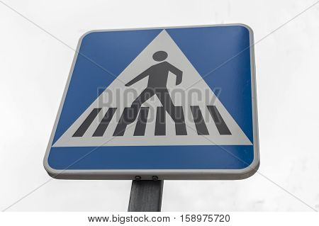Pedestrian crossing traffic sign pole. Isolated over grey sky