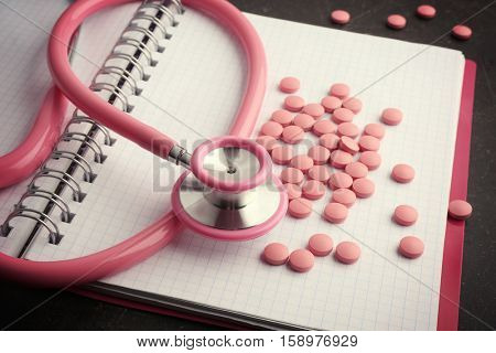 Notebook, stethoscope and pills on dark background