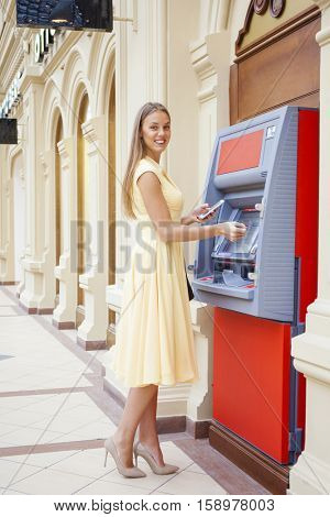 Young happy blonde woman in yellow dress withdrawing money from credit card at ATM
