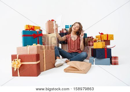 Young beautiful curly girl sitting on floor among gift boxes making selfie with tablet Isolated Copy space
