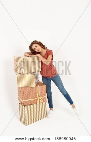 Cheerful young beautiful girl standing next to stack of big gift boxes Isolated Copy space