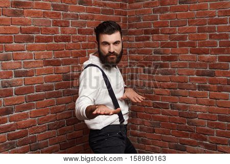 Young handsome man in suit with suspenders dancing posing over brick background. Copy space.