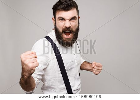 Angry rude young handsome man in suit with suspenders shouting over white background. Copy space.