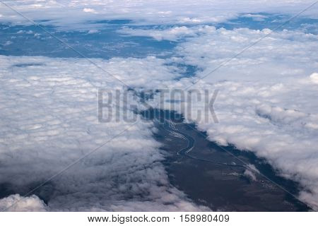 Aerial view from above on river between clouds