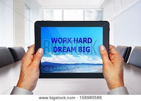 touch pad with image of motto on screen in hands