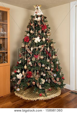 Ornately decorated christmas tree in the corner of a modern living room with cover under the branches