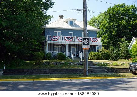 HARBOR SPRINGS, MICHIGAN / UNITED STATES - AUGUST 3, 2016: A two story home, with a front porch and a balcony, on Traverse Street in Harbor Springs.