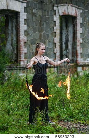 Girl In A Black Suit With Flaming Torches .