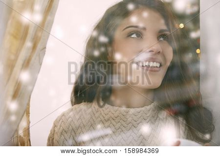 Girl looking at the first snowing from inside
