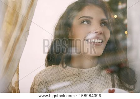 Girl looking outside through a window
