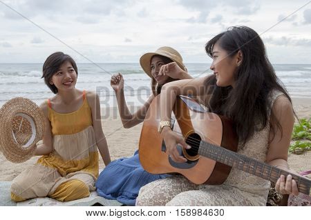 younger asian woman friend vacation relaxing playing guitar and sing a song on sea beach
