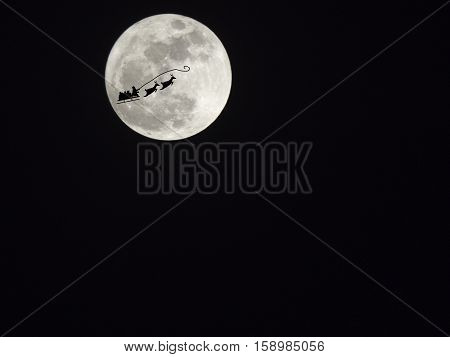 Santa Claus silhouette on full moon in the darkness sky
