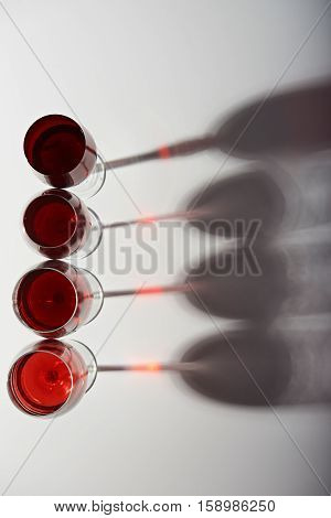 four red wine glasses on line view from top isolated on white