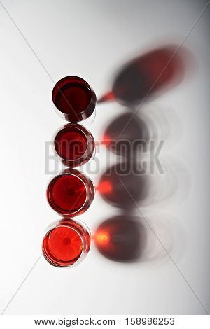 Line of red wine glasses isolated on white background with shadows view from top