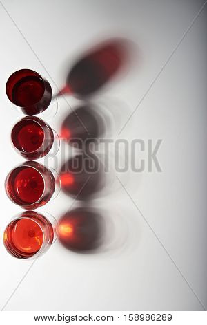 vertical line of red wine glasses with stems isolated on white background view from top