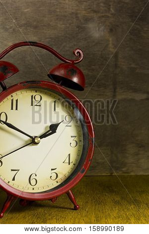 Old red alarm clock on a wooden background