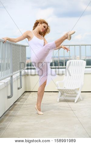 Beautiful girl in white leaning on railing lifted her leg up on the roof of a multistory building